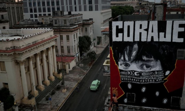 "Cuban artist ""Mr Myl"" paints a mural which reads in Spanish: ""Courage"", amid concerns about the spread of the coronavirus disease (COVID-19) outbreak, in downtown Havana, Cuba, May 20, 2020. REUTERS/Alexandre Meneghini"