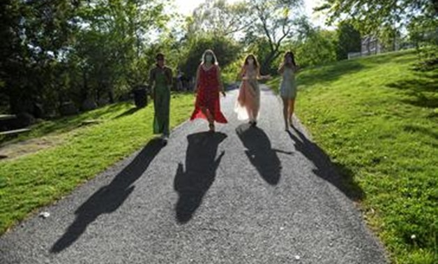 FILE PHOTO: Mila Contreras-Godfrey, Katie Reisig, Gwyn McLear and Melina Bertsekas, high school seniors graduating from Beaver Country Day School, walk through Larz Anderson Park while posing for photographs for Reuters in their prom dresses, after prom w