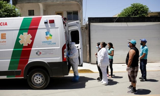 FILE PHOTO: Relatives of a man who died of the coronavirus disease (COVID-19) before being transferred to a hospital are seen near an ambulance transporting the body of their loved one, in Ciudad Juarez, Mexico May 26, 2020. REUTERS/Jose Luis GonzalezREUT