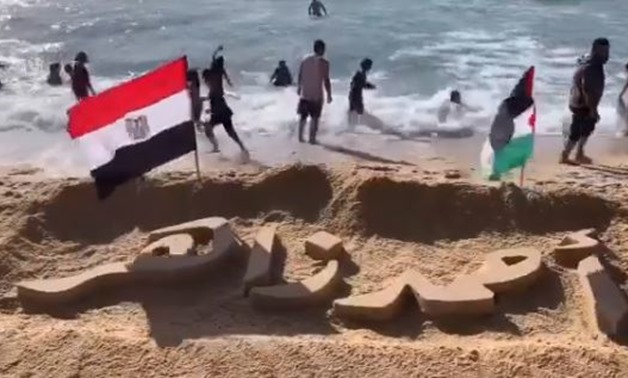Ahmed Zaher's name carved on the sand of one of the Palestinian beaches - ET