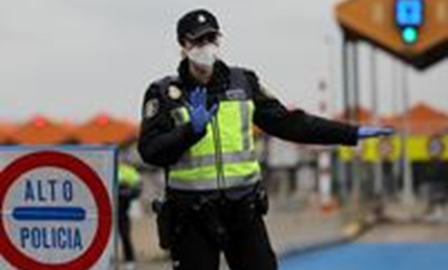 FILE PHOTO: A border police officer gestures as they check vehicles at the last toll gate entering Spain from France, following an order from the Spanish government to set up controls at its land borders over coronavirus, in La Jonquera, Spain March 17, 2