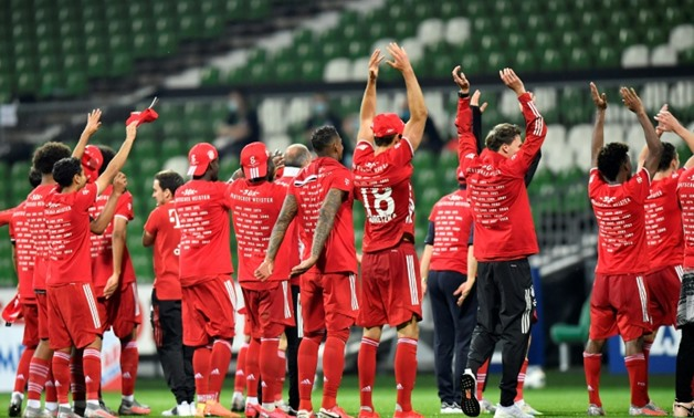 POOL/AFP / Martin MEISSNER Bayern Munich players celebrate in front of near-empty stands after securing an eighth straight Bundesliga title