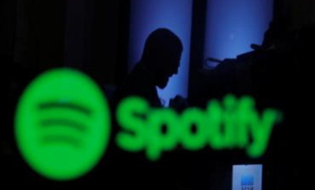 A trader is reflected in a computer screen displaying the Spotify brand before the company begins selling as a direct listing on the floor of the New York Stock Exchange in New York, U.S., April 3, 2018. REUTERS/Lucas Jackson.