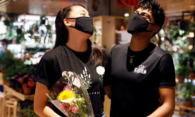 Couple Tareesh 20 and Phebe 16, share a laugh after they are reunited after weeks of ciruit breaker lockdown in Singapore as the city state reopens the economy amid the coronavirus disease (COVID-19) outbreak, June 19, 2020. REUTERS/Edgar Su