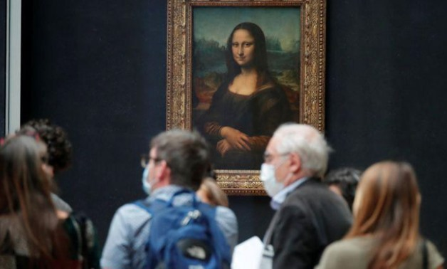 """Media people, wearing protective face masks, stand in front of the painting """"Mona Lisa"""" (La Joconde) by Leonardo Da Vinci at the Louvre museum in Paris as the museum prepares to reopen its doors to the public. Picture taken June 23, 2020. REUTERS/Charles"""