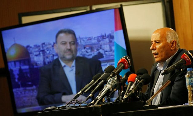 Senior Fatah official Jibril Rajoub speaks as deputy Hamas chief Saleh Arouri appears on a TV screen during a video conference, Ramallah, July 2, 2020. (Reuters)