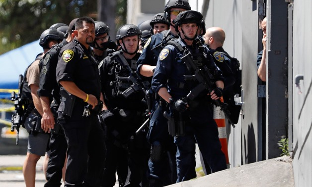 Police officers gather outside a United Parcel Service (UPS) facility after a shooting incident was reported in San Francisco, California, U.S. June 14, 2017. REUTERS/Stephen Lam