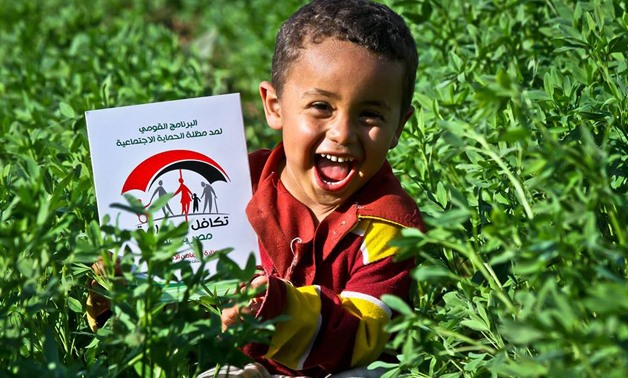 A boy laughs in a field- photo courtesy of Takamul and Karama Facebook Page