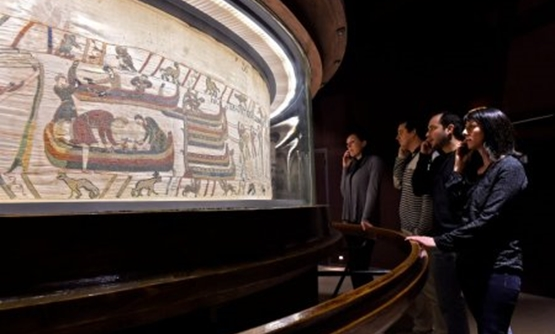People stand in front of the Bayeux Tapestry, an 11th century treasure that tells the tale of how William the Conqueror came to invade England in 1066, in this undated photo provided by the Bayeux Museum in France, on January 18, 2018. Bayeux Museum/Steph