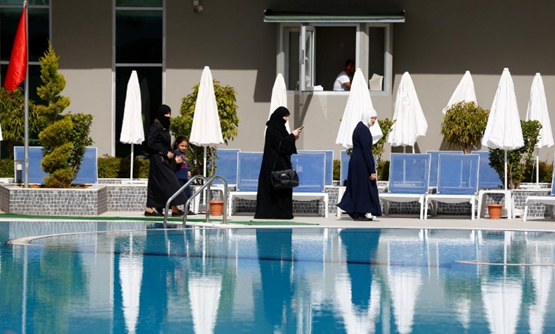 Guests walk by the pool at Elvin Deluxe Hotel, a halal friendly holiday resort, in Alanya, Turkey April 18, 2018. REUTERS/Osman Orsal