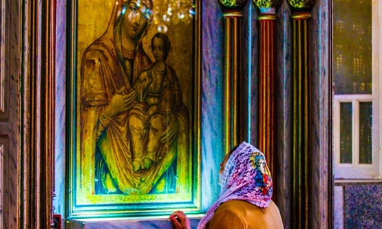 A woman at an icon of Mary and Christ in Muharraq Monastery, Asyut Oct. 15, 2017 – Maher Eskandar