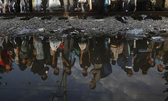 Syrian refugees are reflected in a puddle as they wait for their turn to enter Macedonia at Greece's border. (photo credit: REUTERS)