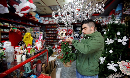 A Palestinian vendor holds a Christmas gift in a shop in Bethlehem in the occupied West Bank November 28, 2018. REUTERS/Mussa Qawasma
