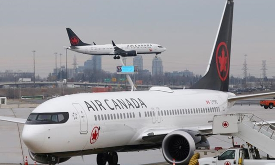 FILE PHOTO - An Air Canada Boeing 737 MAX 8 from San Francisco approaches for landing at Toronto Pearson International Airport over a parked Air Canada Boeing 737 MAX 8 aircraft in Toronto, Ontario, Canada, March 13, 2019. REUTERS/Chris Helgren
