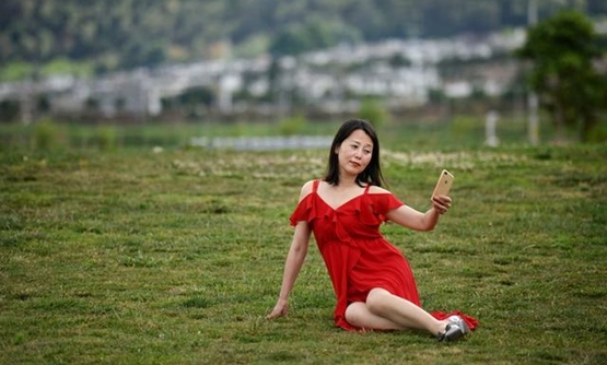 A woman takes selfies with a mobile phone near Erhai Lake in Dali Bai Autonomous Prefecture, Yunnan province, China June 15, 2019. REUTERS/Tingshu Wang