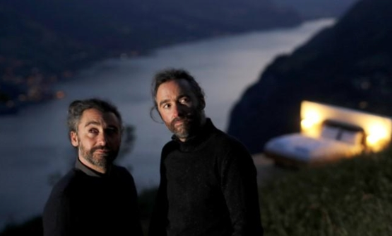 Swiss artists Frank and Patrik Riklin pose in front of the bedroom of their Zero-Real-Estate land art installation, as the outbreak of the coronavirus disease (COVID-19) continues, on an alp in front of the Churfirsten mountain range and Lake Walen near W