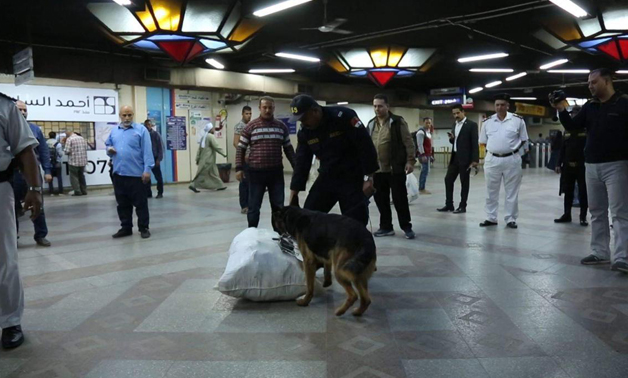 Police officers with guard dogs inspects commuters' bags at a metro station- press photo