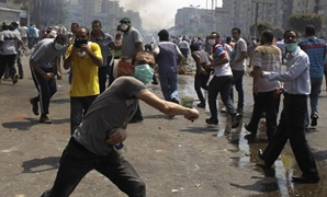 Members of the Muslim Brotherhood throw stones at riot police and army personnel during clashes in Cairo - Reuters