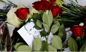A picture taken on July 22, 2017 shows red roses and a picture of Linkin Park frontman Chester Bennington outside the US embassy in Moscow. He killed himself last month on the birthday of his late friend Chris Cornell of Soundgarden-AFP / Maxim ZMEYEV
