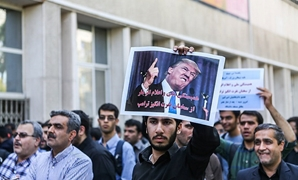 An Iranian student holds an anti-U.S. President Donald Trump poster during a protest against Trump's latest speech on Iran, in Tehran - REUTERS