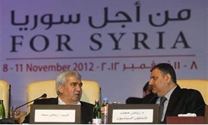 Leading Syrian dissident Riad Seif (L) speaks with former Syrian Prime Minister Riyad Hijab- Reuters