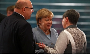 File- Acting German Chancellor Angela Merkel talks with German Environment Minister Barbara Hendricks and Head of Federal Chancellery Peter Altmaier before the meeting with mayors at Chancellery in Berlin, Germany, November 28, 2017. REUTERS/Hannibal Hans