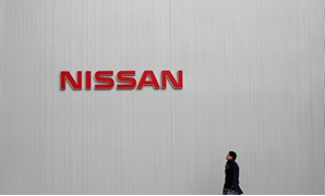 FILE PHOTO: A man walks under the logo of Nissan Motor Co at the company's showroom in Yokohama, south of Tokyo February 8, 2013. REUTERS/Toru Hanai/File Photo