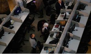 FILE - Employees in the EGX following performance of the trading session on December 12, 2017