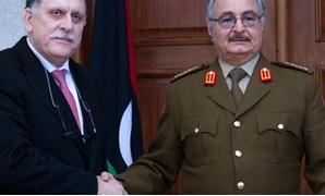 General Khalifa Haftar (R), commander of the armed forces loyal to the internationally recognized Libyan government, shakes hands with the head of the UN backed Libyan Presidential Council, Fayez al-Sarraj, in 2016 – AFP