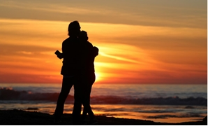 A couple embraces as they watch the sun set in Solana Beach, California, U.S., January 4, 2018. REUTERS/Mike Blake