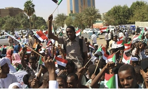 Government supporters gather in front of military headquarters in Khartoum and wave national flags after learning that JEM leader Khalil Ibrahim had been killed. (Reuters)