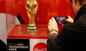 A man takes a picture of the World Cup trophy after a news conference devoted to the FIFA World Cup Trophy Tour in Krasnoyarsk, Siberia, Russia, September 10, 2017. REUTERS/Ilya Naymushin