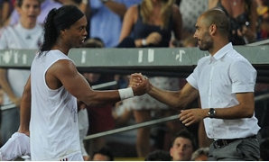 Barcelona's coach Pep Guardiola (L) greets AC Milan's player Ronaldinho after his substitution during a friendly match at Camp Nou stadium in Barcelona August 25, 2010. REUTERS/Albert Gea (SPAIN - Tags: SPORT SOCCER)