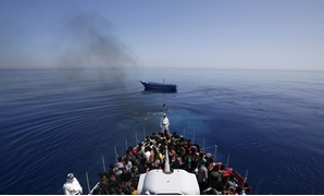 RESCUED: Italian police carry migrants to safety, leaving their leaky boat to drift. REUTERS/Alessandro Bianchi