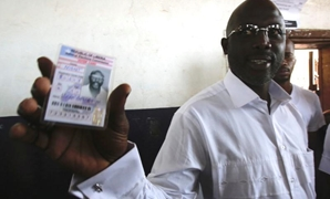 George Weah, former soccer player and presidential candidate of Congress for Democratic Change (CDC) shows his voter's card at a polling station in Monrovia, Liberia October 10, 2017. REUTERS/Thierry Gouegnon