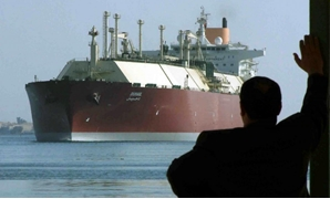 FILE- : FILE PHOTO - A man looks as the world's biggest Liquefied Natural Gas (LNG) tanker, Qatari-flagged DUHAIL as she crosses through the Suez Canal April 1, 2008. REUTERS/Stringer/File Photo