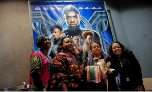 "FILE PHOTO: A group of women pose for a photo in front of a poster advertising the film ""Black Panther"" on its opening night of screenings at the AMC Magic Johnson Harlem 9 cinemas in Manhattan, New York, U.S., February 15, 2018. REUTERS/Andrew Kelly"