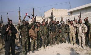 Forces loyal to Syria's President Bashar al-Assad hold up their weapons as they cheer in the town of Safira November 1, 2013. REUTERS/George Ourfalian