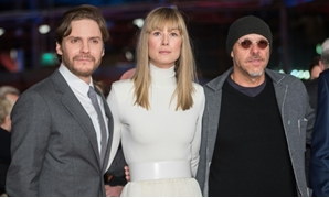 "German actor Daniel Bruehl, English actress Rosamund Pike and Brazilian director Jose Padilha pose on the Berlin red carpet upon arrival for the premiere of the film ""7 Days in Entebbe"""