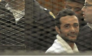 Political activist Ahmed Douma looks on behind bars in Cairo, December 22, 2013 - Reuters