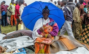 A refugee from the Democratic Republic of Congo sits with her belongings near the United Nations High Commissioner for Refugees (UNHCR) offices in Kiziba refugee camp in Karongi District, Rwanda February 21, 2018. REUTERS/Jean Bizimana