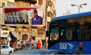 "People walk near a poster of Egyptian President Abdel Fatah al-Sisi of the campaign titled, ""Alashan Tabneeha"" (So You Can Build It), at Sayeda Zainab square in downtown of Cairo, Egypt"