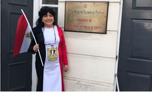 A woman voter wearing a dress of the three Egyptian flag colours outside the Egyptian embassy in London to cast her vote in Presidential election - Egypt Today