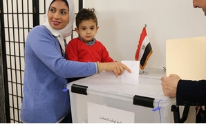 FILE: An Egyptian woman carries her son as she casts her ballot for the Presidential Vote at the polling station of the Egyptian Embassy in the United States