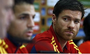 Spain's national soccer player Xabi Alonso (R) looks at his team mate Cesc Fabregas as they attend a news conference during the Euro 2012 soccer tournament in Gniewino, June 25, 2012. REUTERS/Kacper Pempel