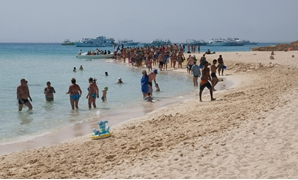 Tourists walking on the beach of Paradise Island of Hurghada. Tourist boats are in the background – CC via Wikimedia Commons/kallerna