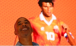 FILE PHOTO: Former Dutch national soccer team captain Ruud Gullit smiles in front of a screen projecting an image of him during a World Cup promotional event at a shopping mall in Hong Kong June 8, 2014. REUTERS/Bobby Yip (CHINA - Tags: SPORT SOCCER WORLD