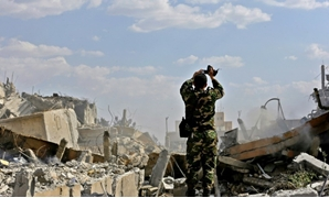 A Syrian soldier inspects the wreckage of a building described as part of the Scientific Studies and Research Centre (SSRC) compound in the Barzeh district north of Damascus, during a press tour organised by the Syrian government after US-led strikes - AF