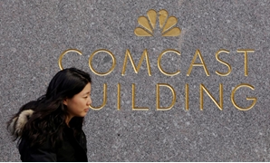 FILE PHOTO: A woman walks past the NBC and Comcast logos on 30 Rockefeller Plaza in midtown Manhattan in New York, U.S., February 27, 2018. REUTERS/Lucas Jackson/File Photo