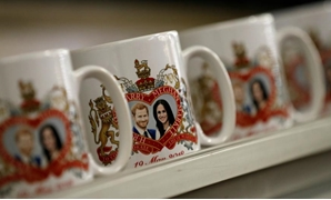 Mugs commemorating the wedding of Britain's Prince Harry and Meghan Markle move along a conveyor belt at the Prince William Pottery Company in Liverpool - REUTERS
